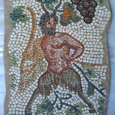 Mosaico Fauno | Arte del Mosaico en piedra. Realizado en técnica mixta, en Opus Vermiculatum y fondo en Opus Tessellatum. Representación de un fauno entre hojas de parra y un racimo de uvas.