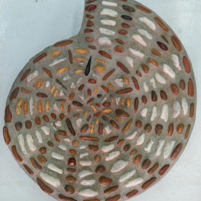 Mosaico con forma de amonite, realizado con guijarros blancos, amarillos y marrones.