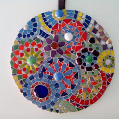 Mandala realizado con diferentes vidrios de colores formando círculos con flores.