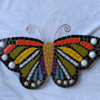 Mosaico de una mariposa de colores con antenas de alambre de cobre.