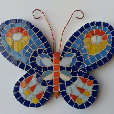 Mosaico de una mariposa de colores en tonos azules, amarillo y naranjas con antenas de alambre de cobre.