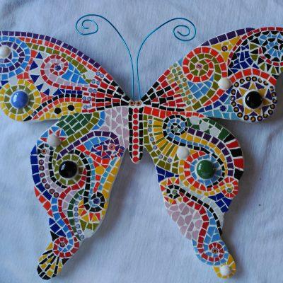 Mariposa compuesta de varios colores con antenas de alambre azul.