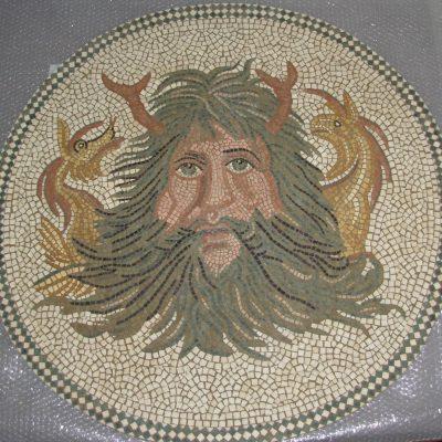 Mosaico Océanos | Arte del Mosaico en piedra. Mosaico realizado en técnica mixta, en Opus Vermiculatum y fondo en Opus Tessellatum. Realizado para encastrar en pared y convertirlo en una fuente, en la boca se pondrá una lengüeta de cobre por donde saldrá el chorro de agua. Reinterpretación de un fragmento Mosaico del Museo Nacional del Bardo (Túnez). Representa la Cabeza del dios Océanos, con sus barbas, pinzas y dos cabezas de dragones a cada lado.