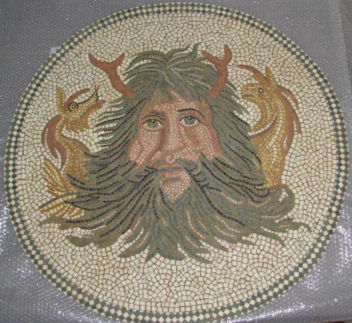 Mosaico Océanos   Arte del Mosaico en piedra. Mosaico realizado en técnica mixta, en Opus Vermiculatum y fondo en Opus Tessellatum. Realizado para encastrar en pared y convertirlo en una fuente, en la boca se pondrá una lengüeta de cobre por donde saldrá el chorro de agua. Reinterpretación de un fragmento Mosaico del Museo Nacional del Bardo (Túnez). Representa la Cabeza del dios Océanos, con sus barbas, pinzas y dos cabezas de dragones a cada lado.