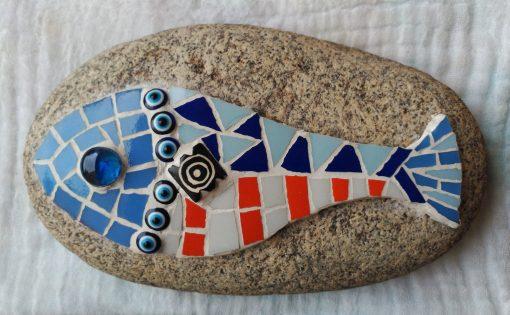Mosaico de un pez en tonos azules y naranjas. Consolidado sobre una piedra para poder utilizarla como tope de puerta.