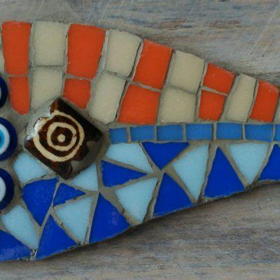 Mosaico de un pez de colores en tonos azueles y naranjas sobre una madera reciclada.