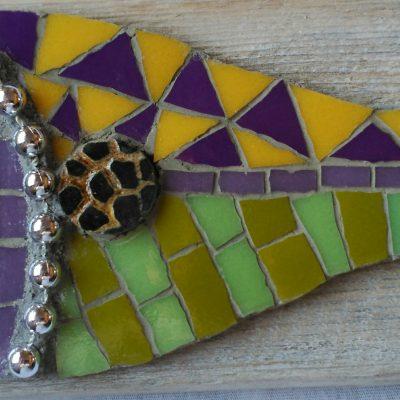 Mosaico de un pez de colores en tonos verdes, violetas y amarillo sobre una madera reciclada.