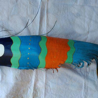 Pez realizado sobre una hoja de palmera, pintado en colores azules, verdes, naranjas y un toque en oro.